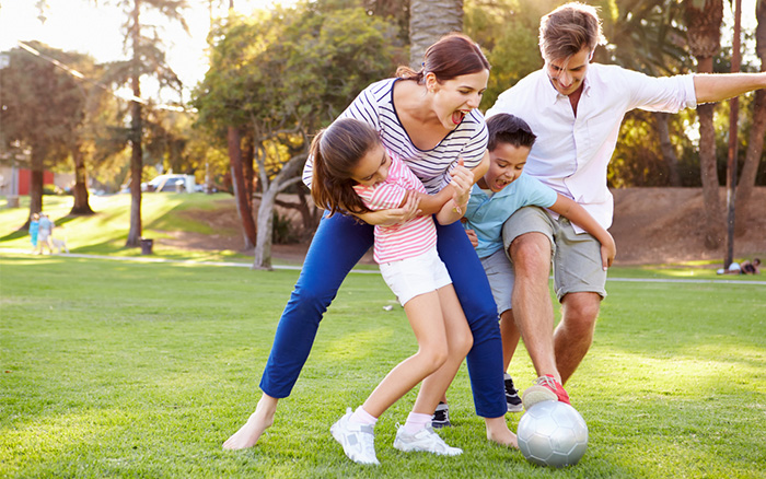 family-playing-football-on-the-lawn-in-garden
